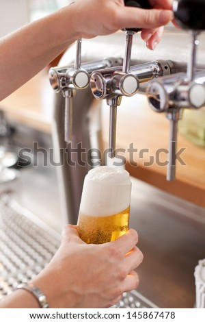 Bartender pouring a pint of frothy draft beer into a glass from a steel spigot on a keg in a bar - stock photo