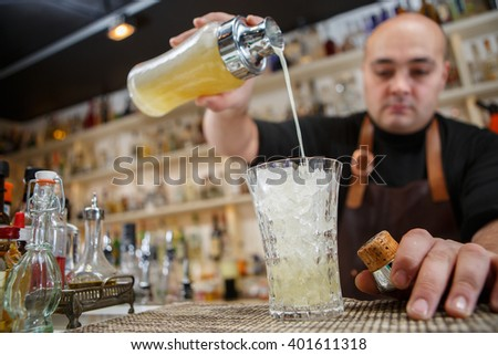 Bartender pouring cocktail into glass at the bar - stock photo