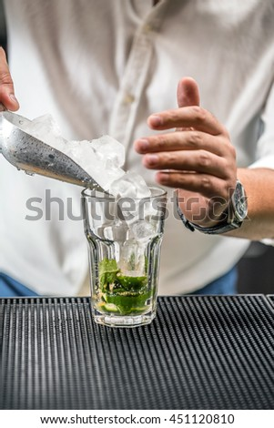 Bartender pouring ice cube in glass - preparing mojito cocktail