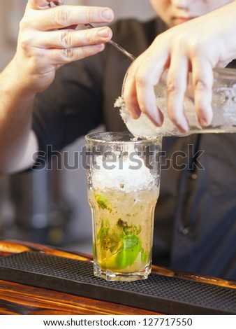 Bartender pouring ice in glass - preparing mojito