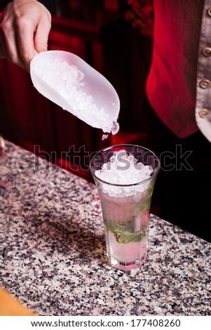 Bartender pouring ice in glass - preparing mojito - stock photo