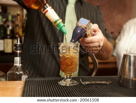 Bartender pouring mixed drink of rum and cola
