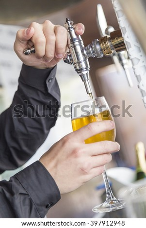 Bartender pours a beer at the bar in the club - stock photo