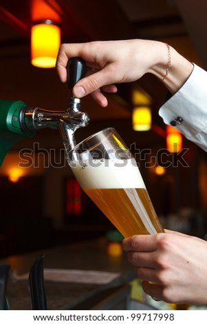 bartender pours beer into glass from tap - stock photo
