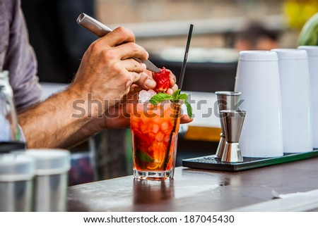 bartender preparing mint and strawberries mojito cocktail on bar