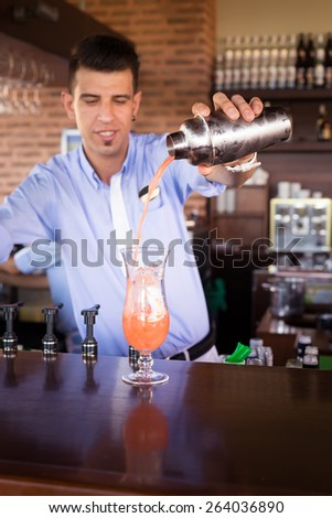 Bartender preparing Sex on the beach cocktail in an outdoor bar. Shollow DOF, focus on shaker and glass, lightly toned - stock photo