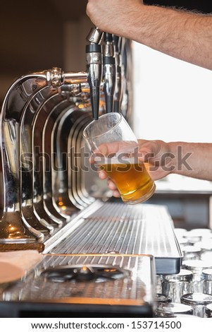 Bartender pulling a pint of beer behind the bar