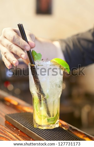 Bartender put a straw in a glass with mojito