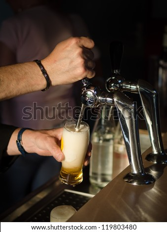 Bartender serving a glass of beer at a bar counter - stock photo