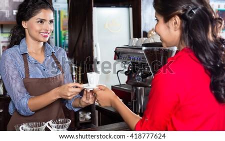 Bartender serving customer in Indian cafe - stock photo