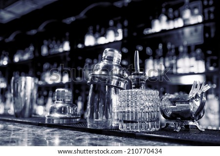 Bartender tools sitting on bar counter, toned image - stock photo