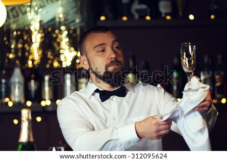 Bartender wipes glasses at work - stock photo