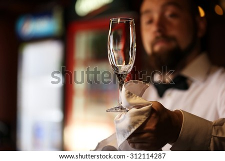 Bartender wipes glasses at work