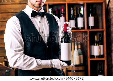 Bartender working on bar background - stock photo