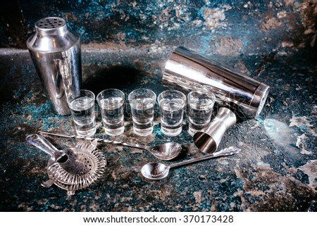 Bartending tools with cocktail shaker, shot glasses and alcoholic drinks. Bar details, nightlife glass alcoholic shots  - stock photo