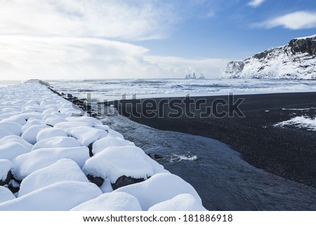 Basalt black sands and a rock jetty covered with fresh snowfall at Vik I Myrdal on the South coast of Iceland
