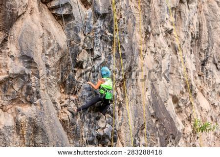 Basalt Challenge Of Tungurahua, Ambitious Girl Climbing A Rock Wall  - stock photo