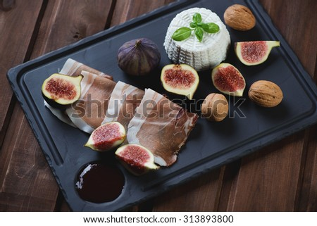 Basalt plate with ricotta cheese, ham, fresh figs and walnuts, selective focus - stock photo