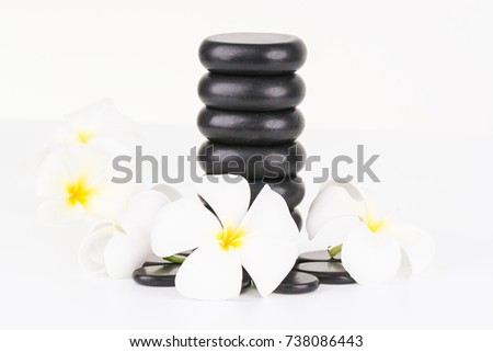 Basalt stones and white Frangipani flowers on white background