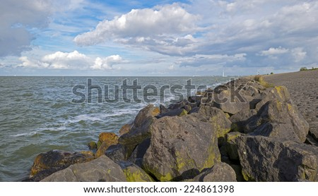 Basalt stones in a stormy lake at fall - stock photo