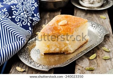 Basbousa (namoora) - arabian semolina cake with almond and honey syrup in iron vintage try on wooden background. Slice of cake - stock photo
