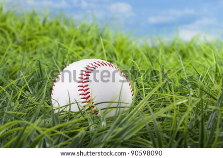 Base ball in grass with blue sky in the background