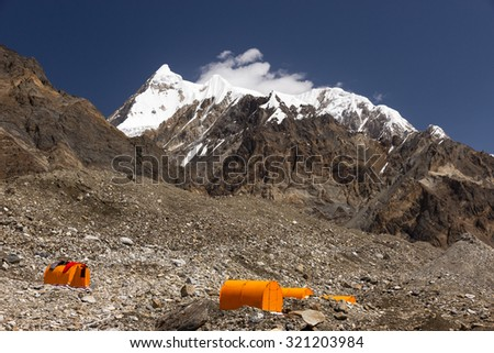 Base Camp of High Altitude Expedition Many Orange Tents Located on Side Rock Moraine of Glacier in Severe Snow and Ice Peaks Landscape - stock photo