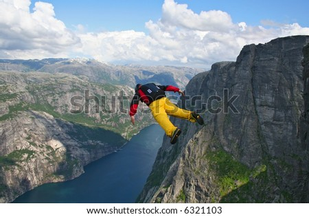 base-jumper falling down to the lyse-fjord. Heliboogie festival at Kjerag, Norway. - stock photo