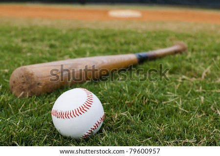 Baseball and old bat on field with base and outfield in background. - stock photo