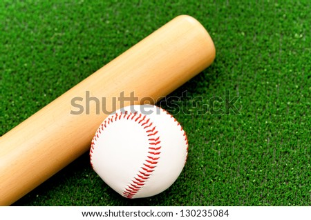 Baseball ball and bat on artificial green grass - stock photo