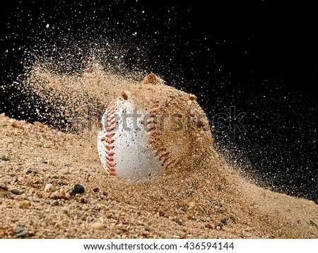 Baseball ball falling in a sand - stock photo