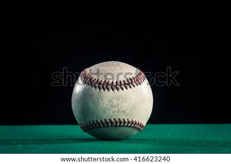 Baseball ball, green and black background