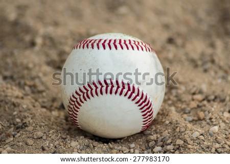 Baseball ball on gravel - stock photo