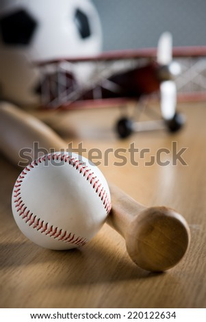 Baseball bat and hardball on wooden floor with toy plane and soccer ball on background.