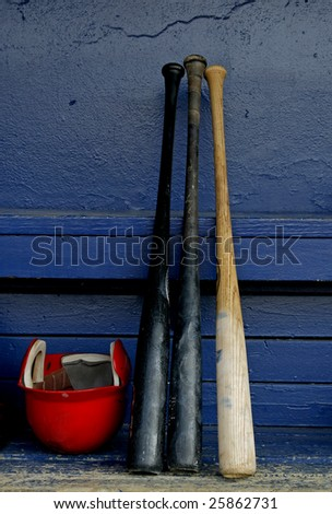 baseball bats and a helmet in an old dugout