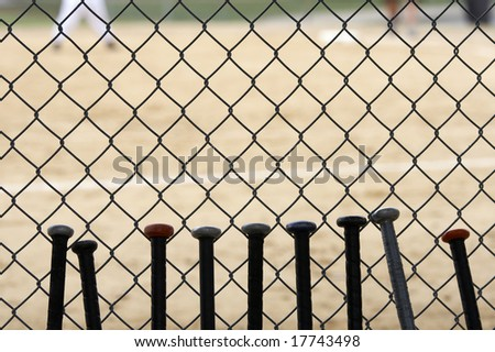 baseball bats learning against dugout fence as game is played - stock photo