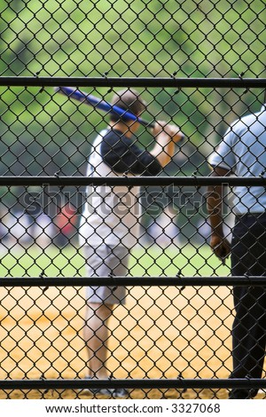 Baseball batter at the plate with focus on fence - stock photo
