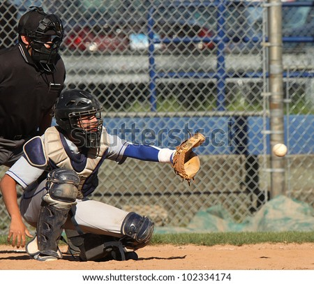 Baseball catcher about to catch a pitched ball. Slight blur on baseball as it flies into his glove. - stock photo