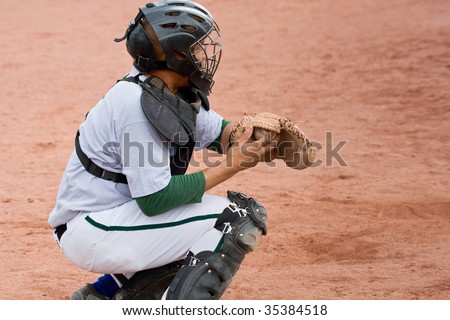 baseball catcher in position with ball in catcher's mitt - stock photo