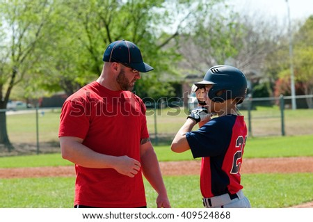Baseball coach giving instruction to teen baseball boy. - stock photo