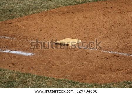 Baseball Field - Dusty 1st base during a baseball game. - stock photo