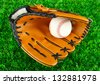 Baseball glove and ball on grass background - stock photo
