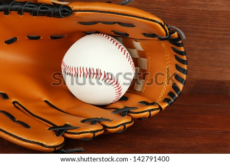 Baseball glove and ball on wooden background - stock photo