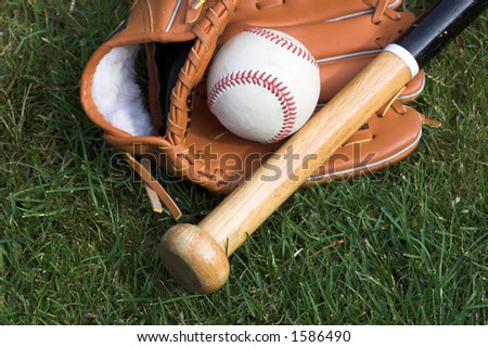 Baseball, glove and bat against a grass background