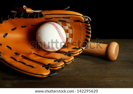 Baseball glove, bat and ball on dark background - stock photo