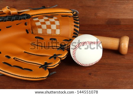 Baseball glove, bat and ball on wooden background - stock photo