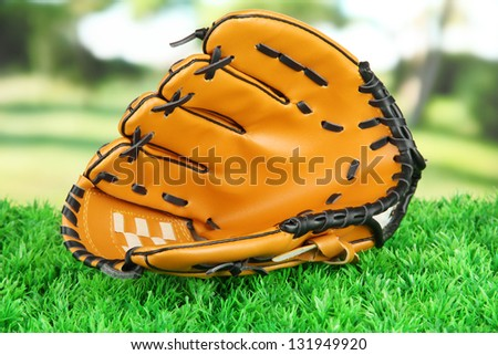 Baseball glove on grass in park - stock photo