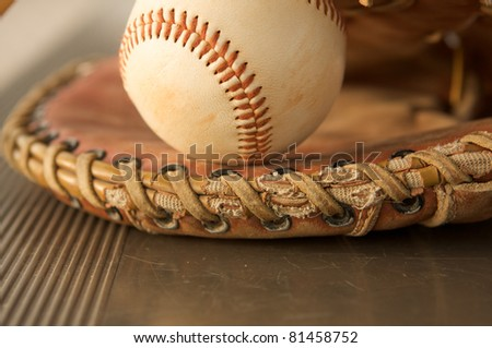 Baseball in a glove close up on the metal bench
