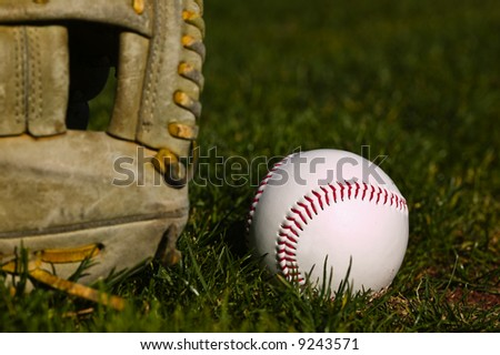 Baseball in a glove sitting on the grass of a field