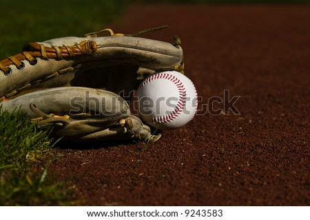 Baseball in a mit sitting on the grass and dirt of a diamond